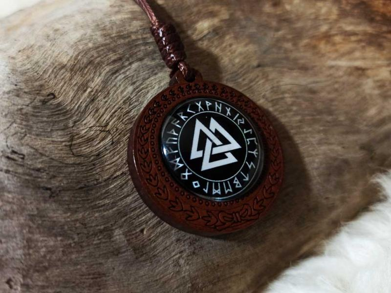 Valknut in the rune circle of ancient Futhark made in wood